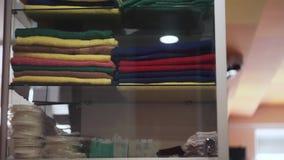 Inclinaison tirée sur les serviettes colorées dans le wordrobe en verre dans le gymnase clips vidéos