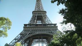 Inclinando abajo en la torre Eiffel poderosa en un parque en París, Francia almacen de metraje de vídeo