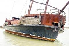 Inclinando el naufragio roto y oxidado abandonado en orilla cercana de la ensenada, Imagen de archivo libre de regalías