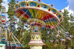 Inclinando giro aereo della sedia all'annuale, giro dell'oscillazione alla fiera in un parco di divertimenti con i pini immagini stock libere da diritti