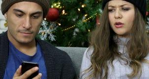 Inclinando os pares caucasianos que falam sobre o smartphone vídeos de arquivo