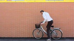 Inclinando uma bicicleta contra uma parede de tijolo vídeos de arquivo