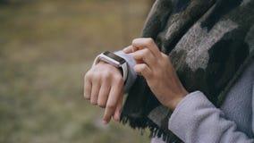 Inclinazione del primo piano sul colpo della ragazza dello studente della corsa mista che usando smartwatch Fotografie Stock