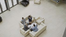 Incline abajo de la opinión superior el grupo de hombres de negocios de los colegas que discuten las cartas financieras que se si metrajes