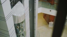 Incline abajo de los colegas de la empresaria y del hombre de negocios que hablan en elevador móvil en centro de negocios moderno metrajes