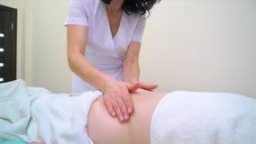 Incline abajo de masajista de sexo femenino en abdomen de masaje uniforme de la mujer joven almacen de video