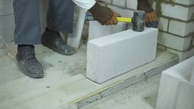 Incline acima do construtor que coloca o primeiro bloco de acordo com a marca na funda??o do assoalho video estoque
