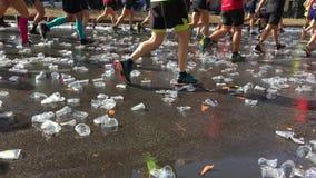 Incline acima dos copos plásticos vazios que desarrumam Berlin Street nos pés de povos de corrida durante Berlin Marathon, em set vídeos de arquivo