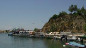 Incline de la bandera griega para abrigarse en los thassos Grecia del puerto del limenaria almacen de video