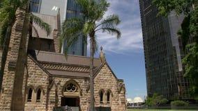 Incline de rascacielos modernos a la catedral de St Stephen en Brisbane almacen de metraje de vídeo