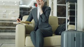 Incline para arriba de la empresaria alegre rubia que se sienta en butaca en el pasillo del hotel que habla el teléfono móvil y q almacen de metraje de vídeo