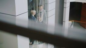 Incline para arriba de los colegas de la empresaria y del hombre de negocios que hablan en elevador móvil durante descanso para t