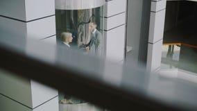 Incline para arriba de los colegas de la empresaria y del hombre de negocios que hablan en elevador móvil y salga de él en negoci almacen de video