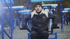 Incline para arriba del hombre joven del atleta que hace ejercicio en el gimnasio al aire libre en parque del invierno fotos de archivo libres de regalías