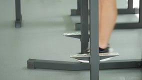 Incline para baixo de um homem farpado novo com um torso desencapado que faz o pé que levanta em uma barra horizontal em um gym vídeos de arquivo