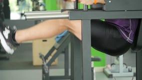 Incline para baixo de um homem farpado novo com um torso desencapado que faz o pé que levanta em uma barra horizontal em um gym video estoque