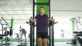 Incline para baixo de um homem novo com um torso desencapado que faz o pé que levanta em uma barra horizontal em um gym filme