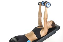 Incline Press 2. A female fitness instructor demontsrates the finishing position of the incline dumbbell press Stock Image