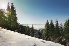 Incline-se com neve e as nuvens frescas abaixo das montanhas imagem de stock