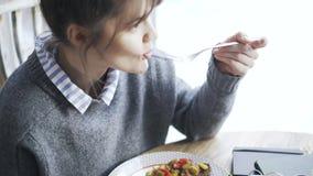 Incline verduras para arriba de una mujer que come fritas o conservadas en vinagre en un café almacen de metraje de vídeo