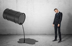 Inclined barrel with black liquid oil pouring out of it on and dissapointed sad businessman. An inclined barrel with black liquid pouring out of it on a grey Royalty Free Stock Photography