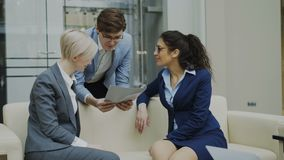 Inclinez de l'homme d'affaires gai parlant et discutant au sujet du rapport financier avec les collègues féminins d'affaires s'as