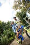 Inclinez l'image du père aidant le fils pour la bicyclette de monte Images stock
