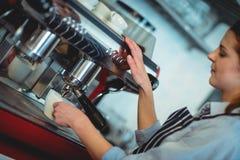 Inclinez le tir du barman utilisant la machine d'expresso pour verser le café dans la tasse Images libres de droits