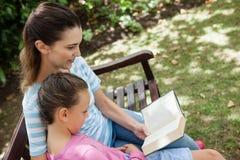 Inclinez le tir du roman de lecture de mère à la fille sur le banc en bois Images libres de droits