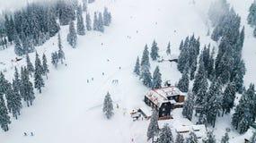 Inclinez pour abaisser des skieurs et des surfeurs dans la station de sports d'hiver Photographie stock libre de droits
