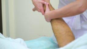 Inclini giù del massaggiatore femminile nel piede di massaggio uniforme dell'uomo nel salone della stazione termale video d archivio