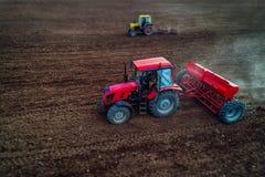Inclini lo spostamento della vista aerea dei trattori che lavorano al fie del raccolto Fotografie Stock Libere da Diritti