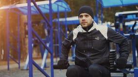 Inclini su di giovane uomo dell'atleta che fa l'esercizio alla palestra all'aperto nel parco dell'inverno Immagine Stock Libera da Diritti