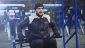 Inclini su di giovane uomo dell'atleta che fa l'esercizio alla palestra all'aperto nel parco dell'inverno Immagini Stock Libere da Diritti