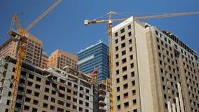 Inclini su panorama di alte costruzioni in costruzione nel centro della città moderna nel giorno soleggiato stock footage