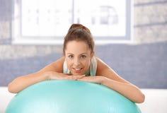 Inclinzione femminile attraente sul sorridere del fitball Immagine Stock