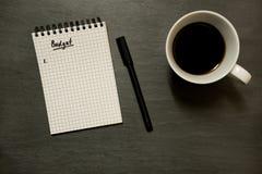Inclua no orçamento a lista no bloco de notas espiral gridded com xícara de café, no tampo da mesa da ardósia - de cima de, mínim imagem de stock royalty free