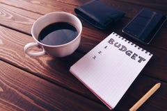 Inclua no orçamento a lista no bloco de notas, no telefone celular, no malote e na xícara de café na madeira escura fotografia de stock
