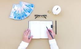 Inclua no orçamento o planeamento, caderno, dinheiro, mealheiro, vista superior, na tabela fotografia de stock