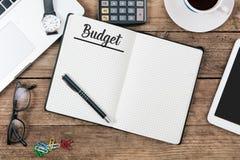 Inclua no orçamento o texto na almofada de nota, mesa de escritório com informática, h fotografia de stock royalty free