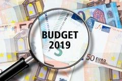 Inclua no orçamento 2019, vista através de uma lupa na inscrição no fundo de cédulas do Euro Finança do negócio fotografia de stock royalty free