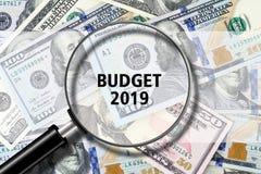Inclua no orçamento 2019, vista através de uma lupa na inscrição no fundo das notas de dólar Finança do negócio fotos de stock