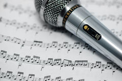 The included microphone is on the musical notation. Included is a metal microphone on white paper with notes Royalty Free Stock Photos
