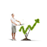 Income concept. Young attractive businesswoman cutting lawn in shape of graph Royalty Free Stock Photos