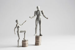 Income inequality concept shown with figurines. Income inequality concept shown with realistic male and female figurines standing on piles of coins. Female stock images