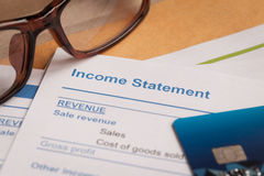 Income statement letter on brown envelope and eyeglass, business Stock Photos