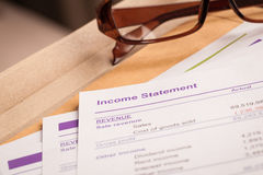 Income statement letter on brown envelope and eyeglass, business Stock Photography