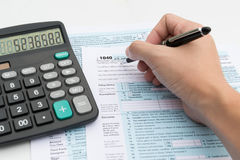 Income tax. Filling out income tax forms with calculator and pen stock photography