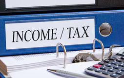 Income and Tax - blue binder with text in the office Stock Photography