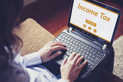 Income tax declaration in a laptop screen. Woman using a laptop Royalty Free Stock Image